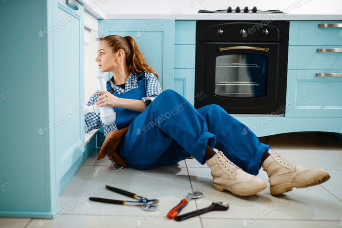 Cute female plumber in uniform holds drain pipe