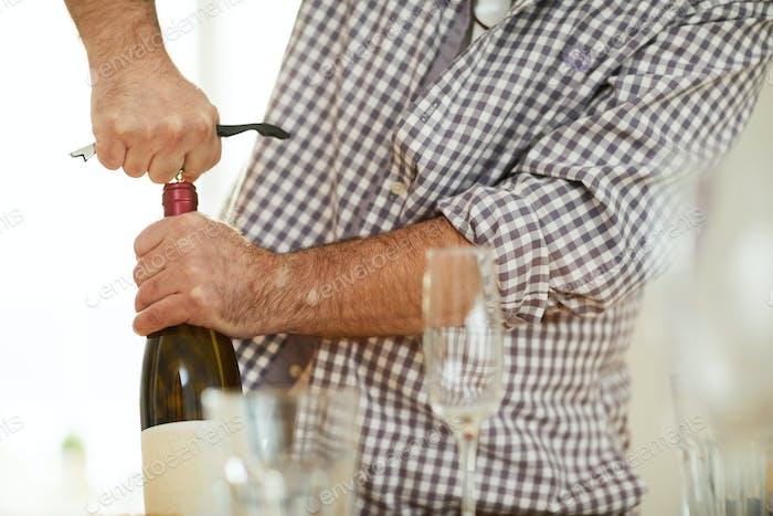 Drawing cork from wine bottle