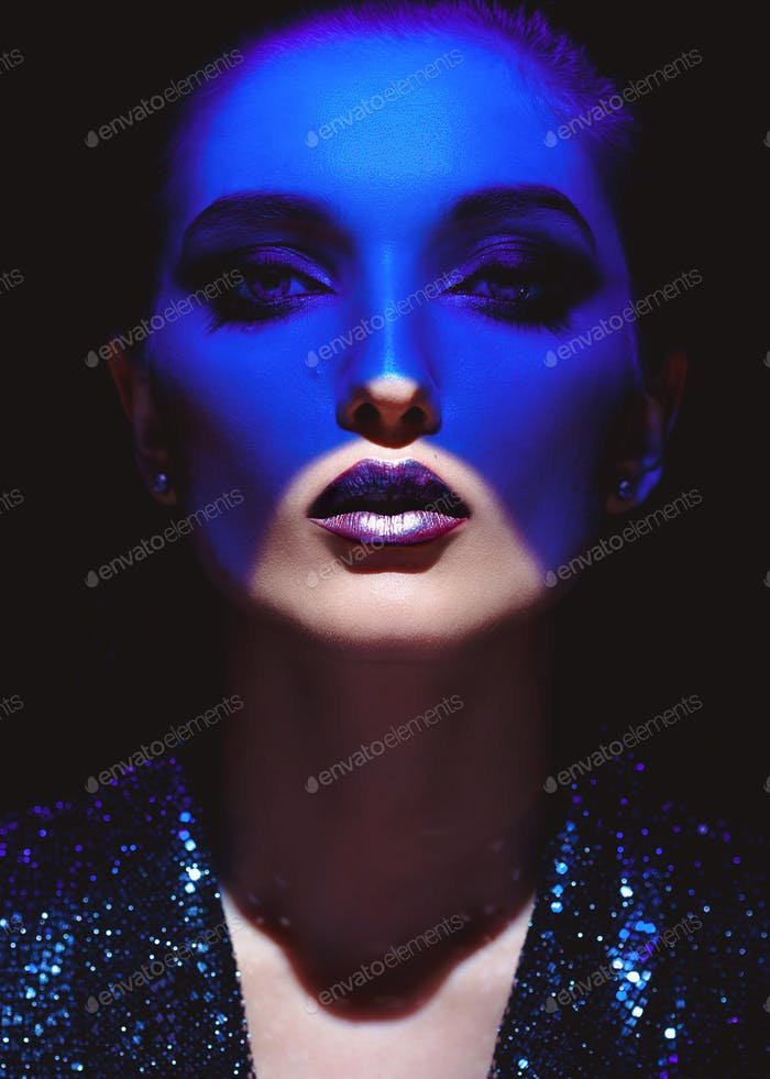 Portrait of fashion girl with stylish makeup and blue neon light on her face on the black background