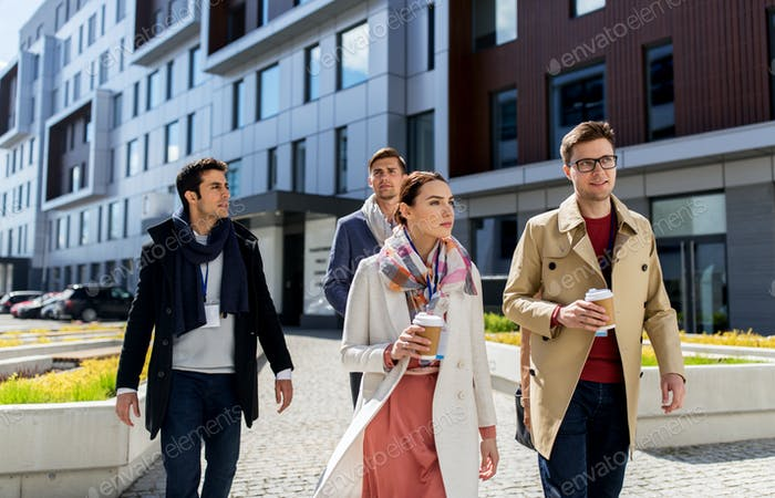 people with coffee and conference badges in city