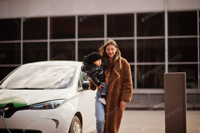 Young mother with child charging electro car at the electric gas station.