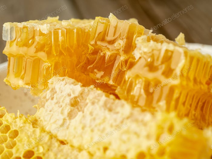 honey in honeycomb, close-up, on white ceramic plate, on wooden rustic table,