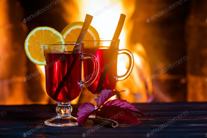 Two glasses of hot mulled wine with spices on wooden table against fireplace.