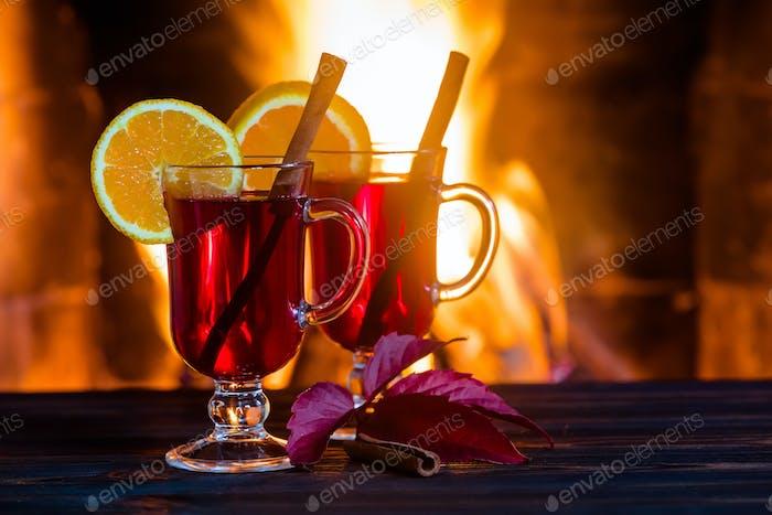 Zwei Gläser heißen Glühwein mit Gewürzen auf Holztisch gegen Kamin.