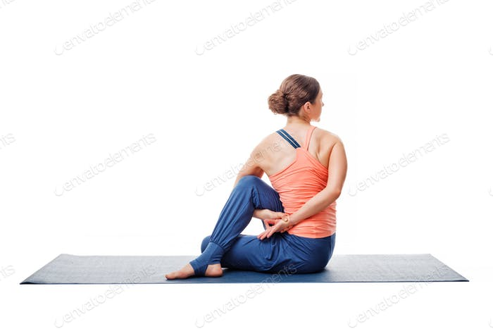Woman practices yoga asana  Ardha matsyendrasan