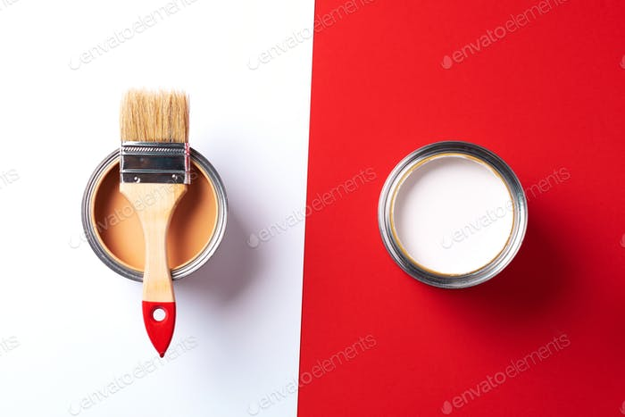 Wooden paint brush, open paint cans on trendy red and white background. Top view, copy space
