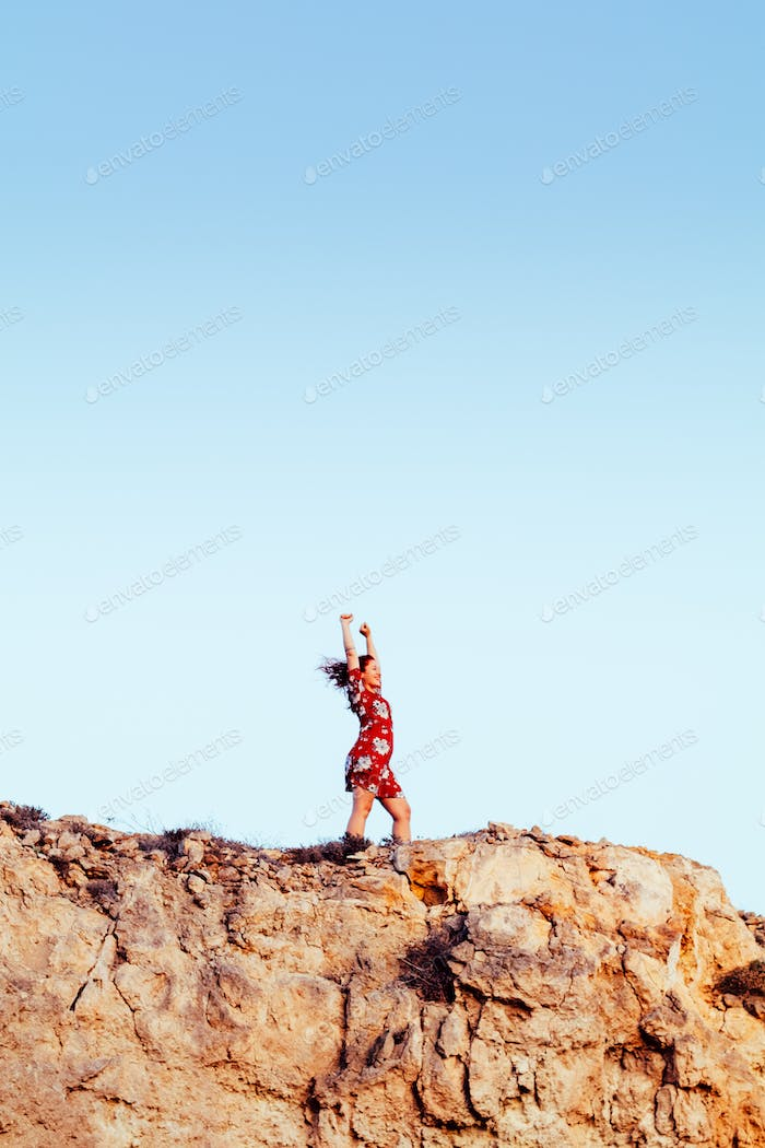 Young girl with red dress on cliff's edge with raised hands and looking to a sky
