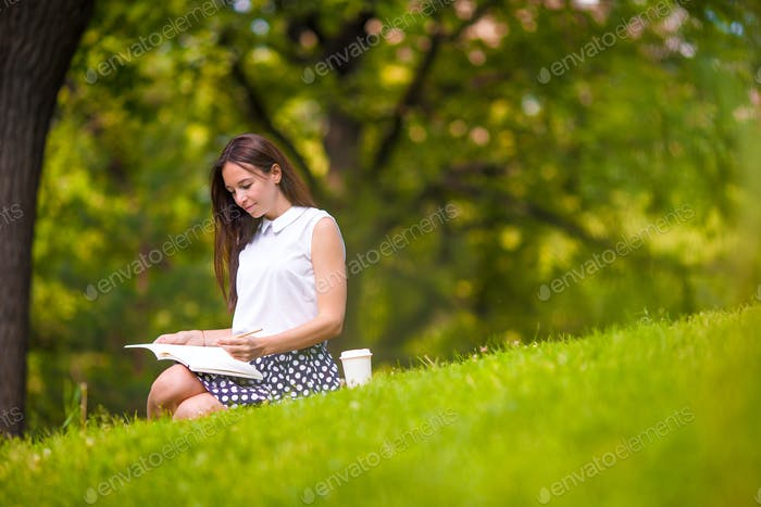 Young woman relaxing with coffee in park reading a book