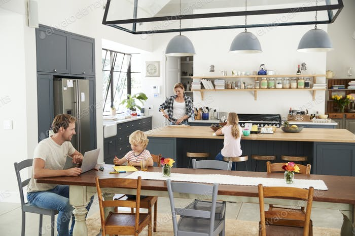 Young white family busy in their kitchen, elevated view