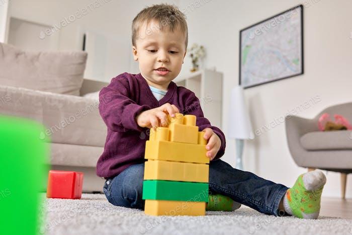 Niño feliz jugando constructor colorido en el suelo en la sala de estar moderna.