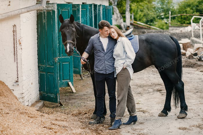 Cute loving couple with horse on ranch