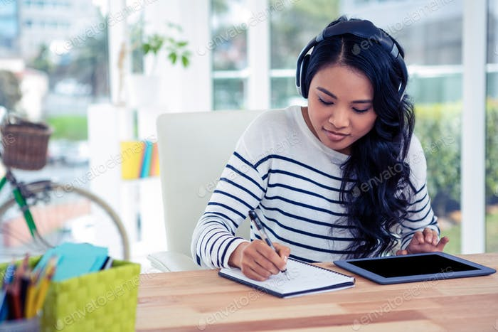 Smiling Asian woman with headphones writing on notepad in office