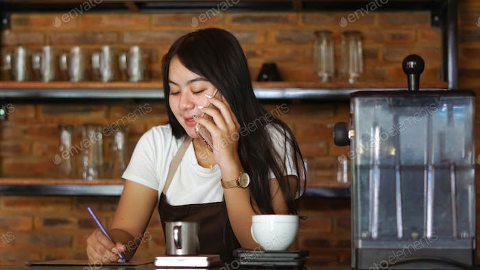 Asian woman barista wear apron talking and receive order from customer on cellphone at coffee shop.