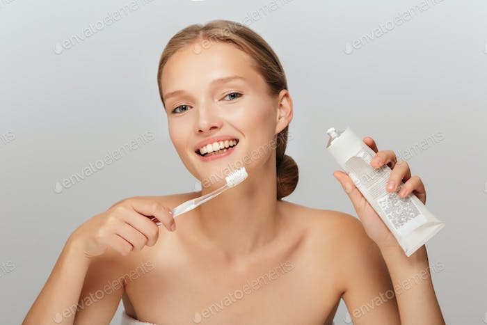 Portrait of young joyful lady without makeup holding toothpaste