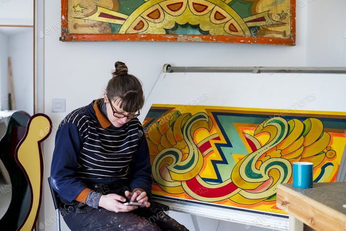 Woman artist working sitting by a drawing in progress at drawing table in a workshop, checking her