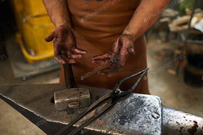 Dirty hands of blacksmith