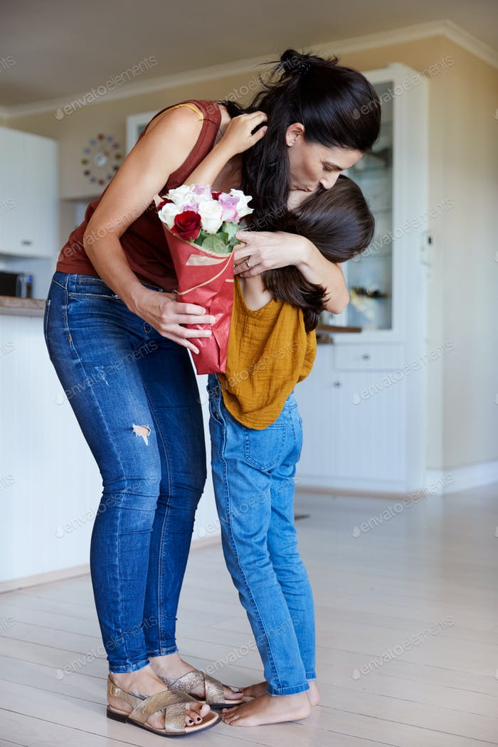 Daughter embracing her mother after giving her flowers on her birthday, full length, vertical