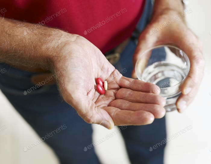 Senior Man Taking Healthcare Medicine Pills With Water