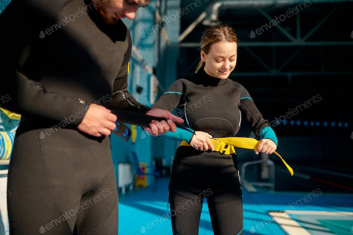 Woman and male instructor tries on scuba gear