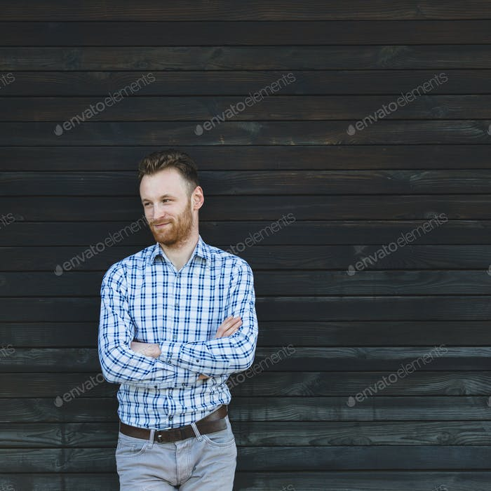 Portrait of young fashionable man against wooden wall