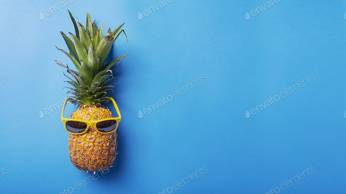 Fresh pineapple with a yellow sun glasses