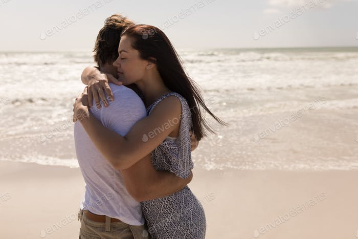 Side view of romantic young couple embracing each other on beach in the sunshine