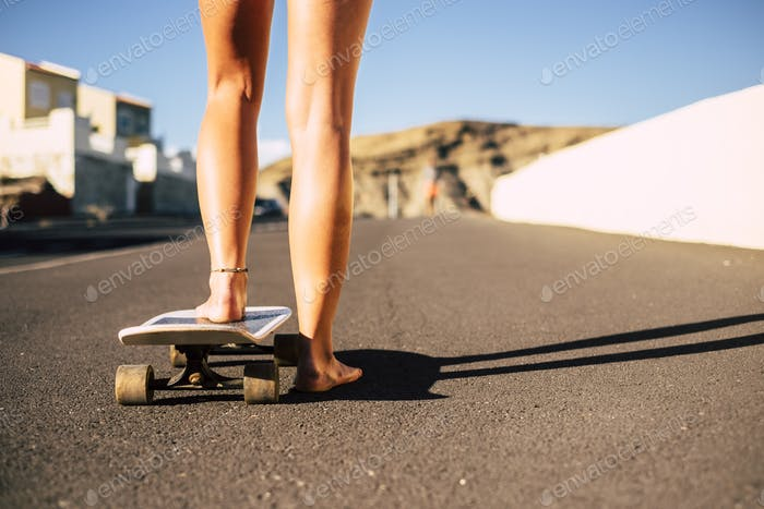 pair of legs barefoot young woman ready to start with the skateboard on the asphalt