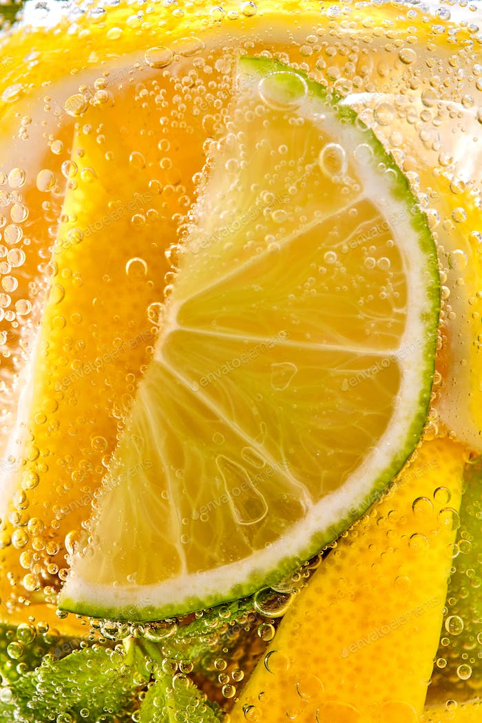 In a clear glass mint leaf, slices of lime and lemon with bubbles. Macro photo of summer drink