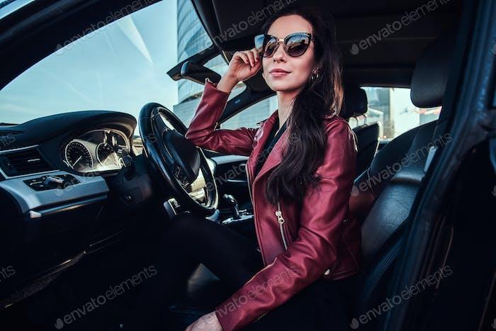 Attraktive nachdenkliche Frau in roter Jacke und Sonnenbrille posiert in ihrem Auto