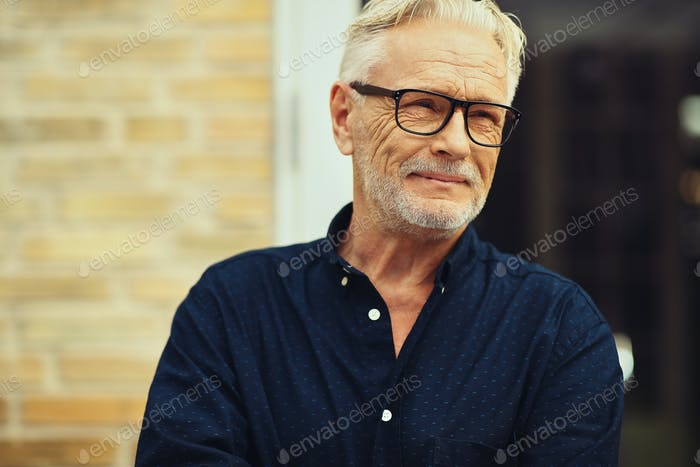 Smiling senior man standing in his yard deep in thought