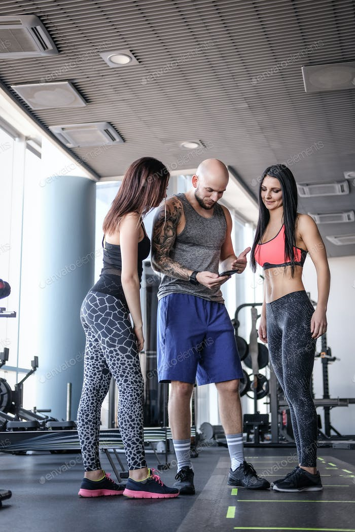 Two beautiful girls with their coach browsing something in the smartphone in modern fitness club