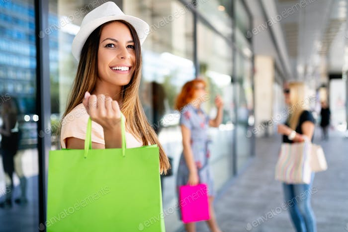 Young happy attractive girls with shopping bags in the city