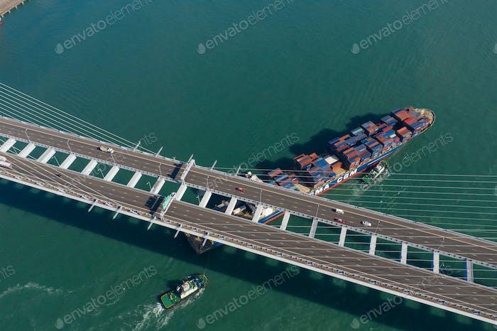 Kwai Tsing, Hong Kong 04 December 2019: Top view of cargo ship pass though suspension bridge
