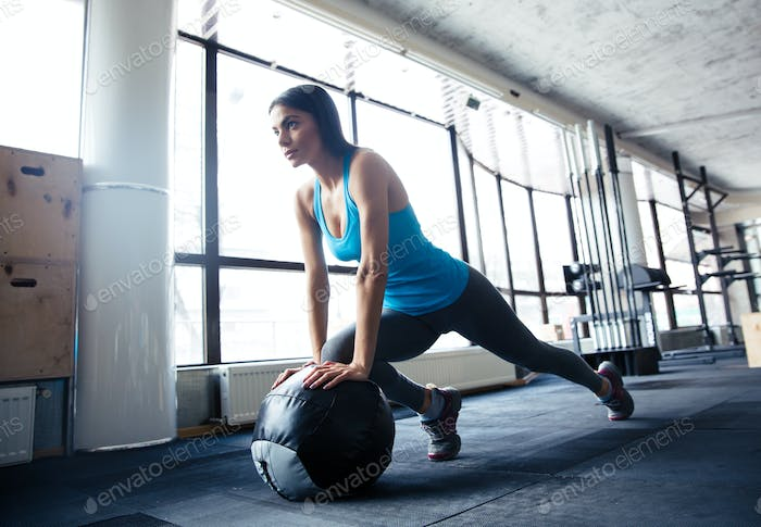 Young woman doing exercise with fit ball