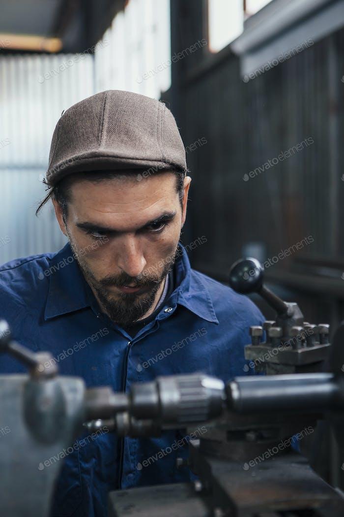 Serious man looking at working machine