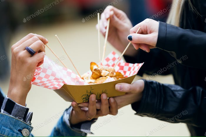 Group of friends visiting eat market and eating potatoes in the