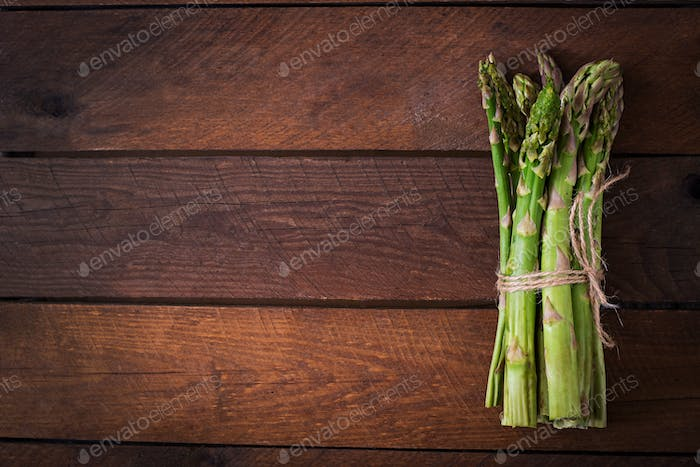Bunch of fresh asparagus on a wooden background. Top view