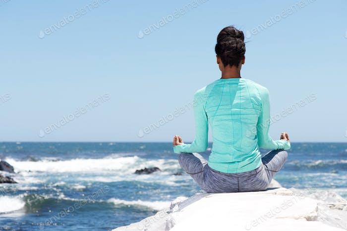 hinter Yoga Frau am Strand