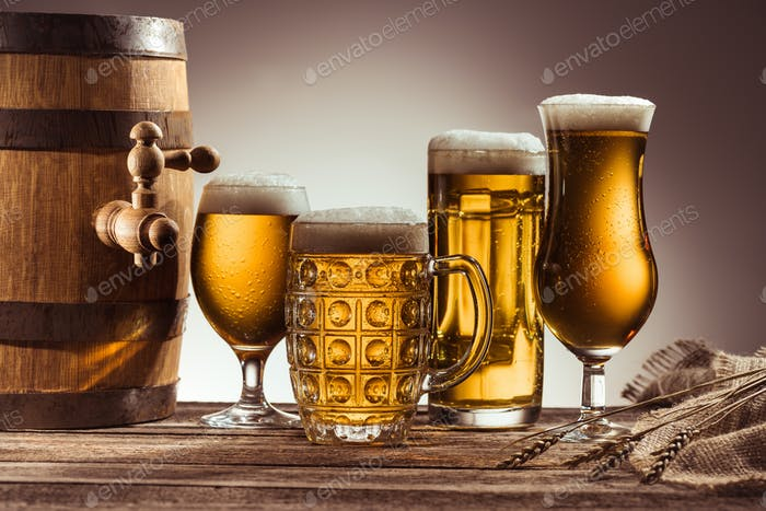 barrel and assortment of beer in glasses on wooden tabletop with wheat ears