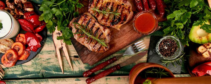 Banner with Steak pork grill on wooden cutting board with a variety of grilled vegetables