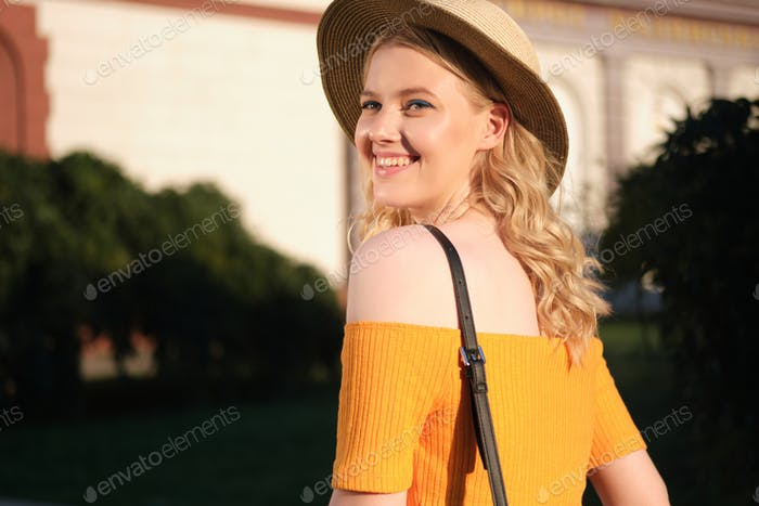 Portrait of beautiful romantic blond girl in hat joyfully looking away on city street