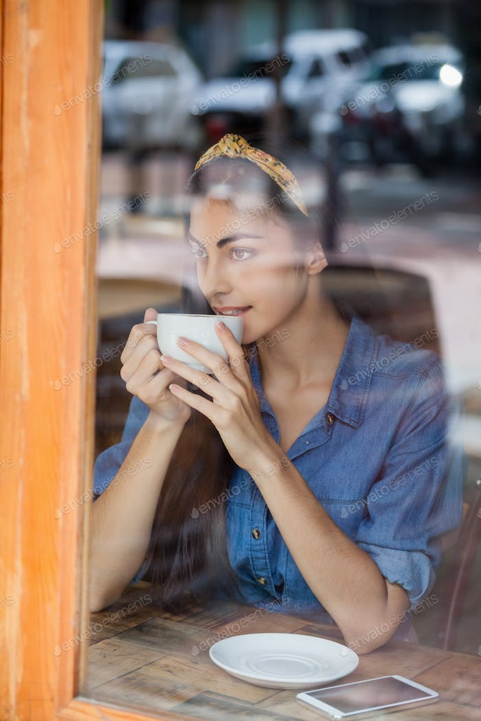 Thoughtful woman drinking coffee in cafe shop