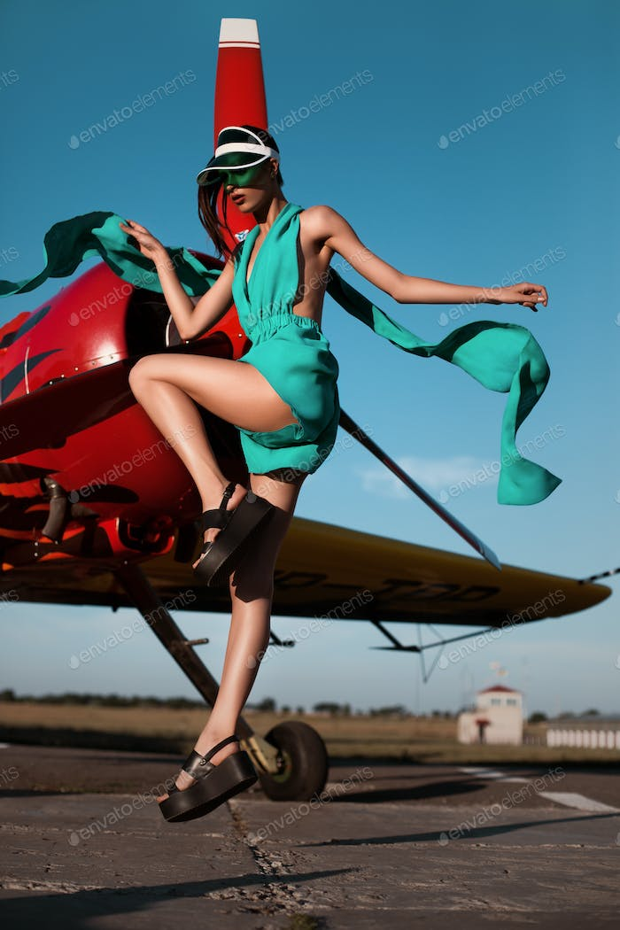 Fashion pilot girl in a visor posing next to propeller plane at runway during sunset