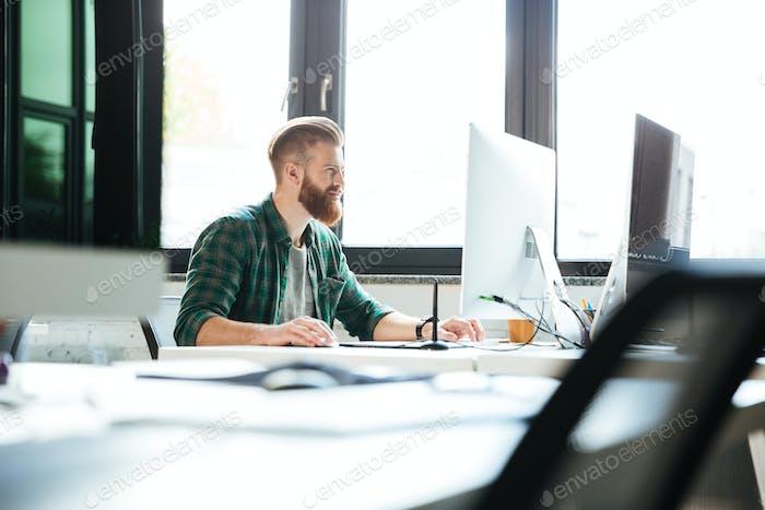 Handsome man work in office using computer.