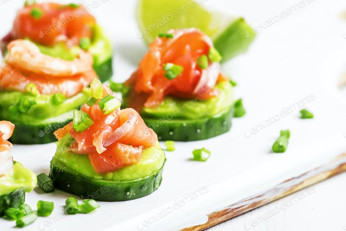 Canape with cucumber, avocado mousse, salmon and shrimp on white wooden background