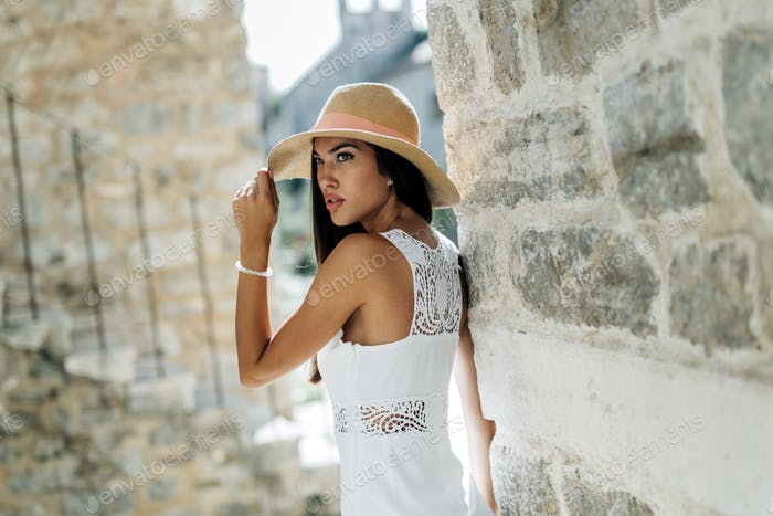 Fashion model posing in street of rustic town
