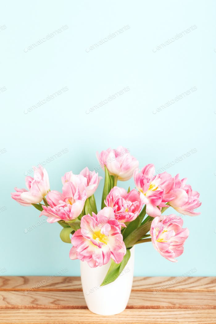 Bouquet of Pink Tulips in White Vase on Wooden Table.