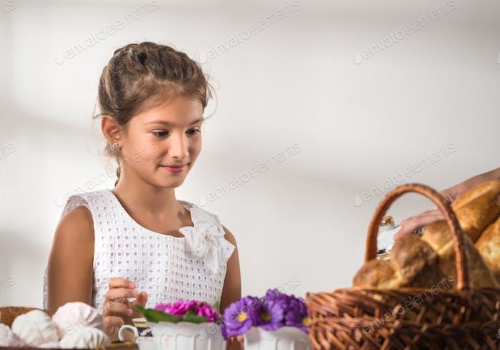 Cute little girl in a white sundress drinks tea