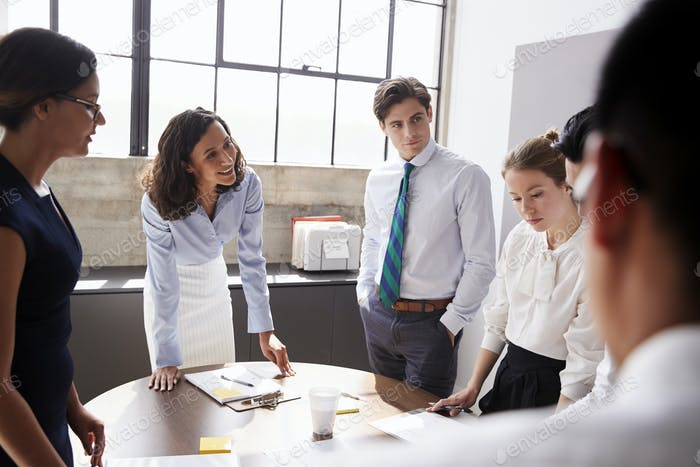 Smiling white female manager listens to team in meeting room