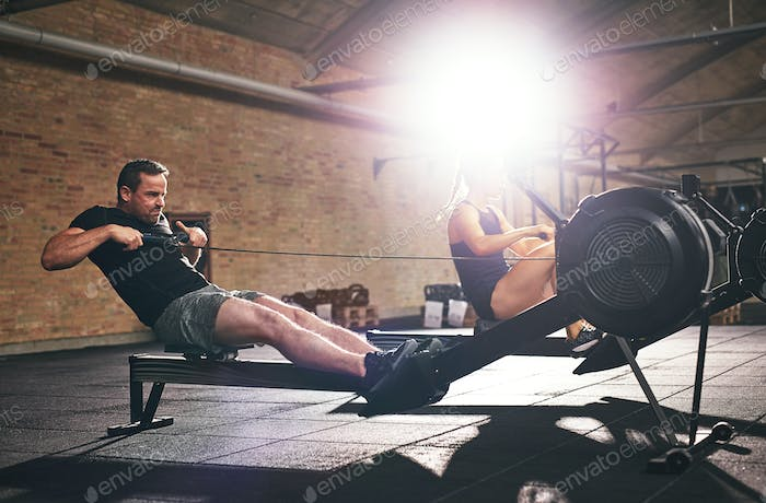Two sportsmen training hard on rowing machines